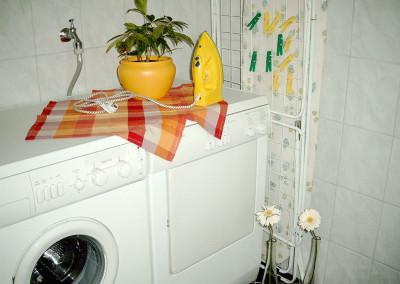 Hauswirtschaftsraum mit Waschmaschine und Trockner sowie Gäste-WC